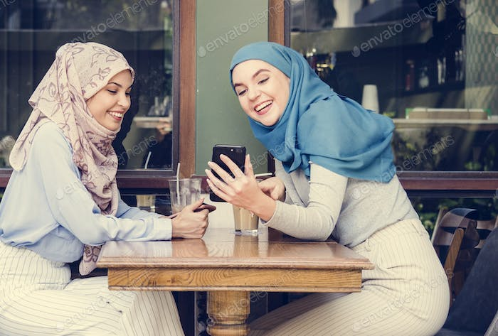 Islamic friends talking and looking on the smart phone