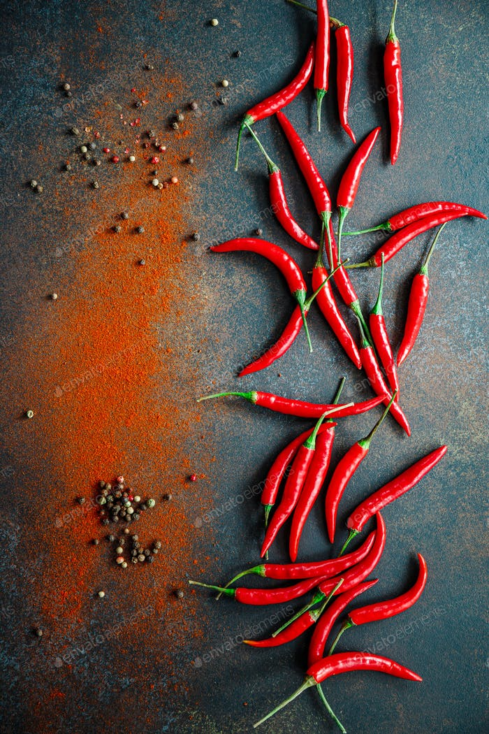 A lot of chili peppers on a kitchen table.