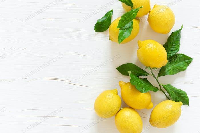 Fresh lemons with leaves on white wooden background,  summer lemonade ingredient