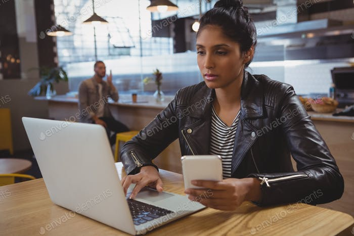 Woman with phone using laptop in cafe