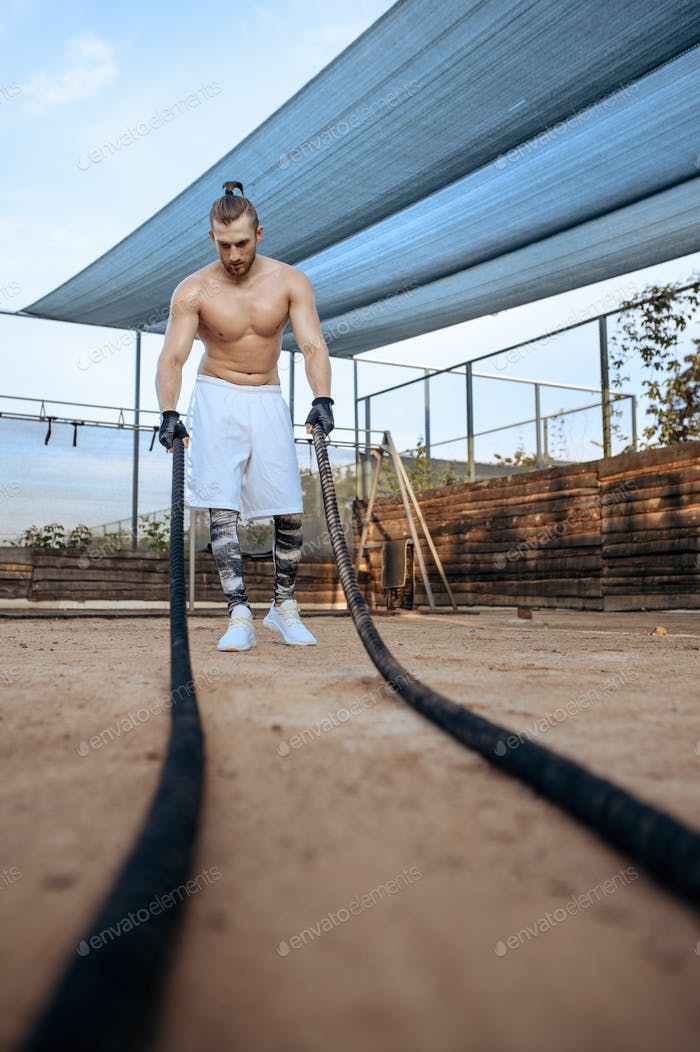 Muscular man doing exercise with ropes, crossfit
