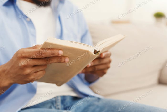 Black male student reading book at home