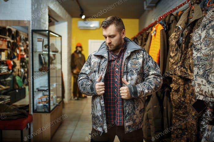 Человек пытается на униформу на витрине в оружейный магазин