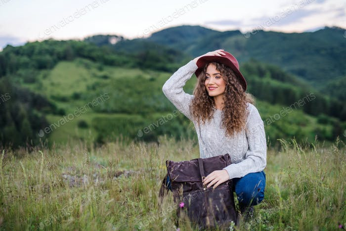 Young tourist woman traveller with backpack in nature, resting.