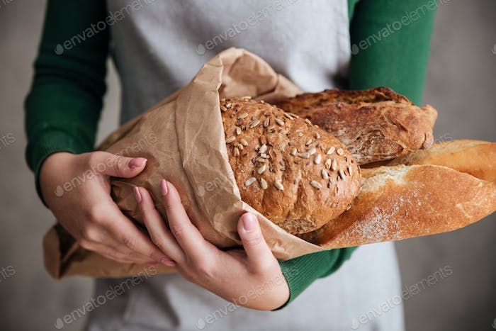 Close up photo of female baker holding bag with bread