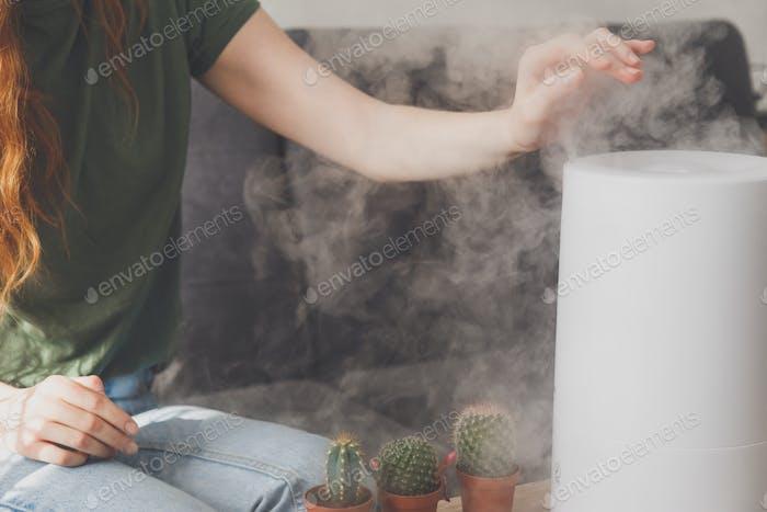 Gesunde Luft. Der Luftbefeuchter verteilt Dampf im Wohnzimmer. Frau hält Hand über Dampf