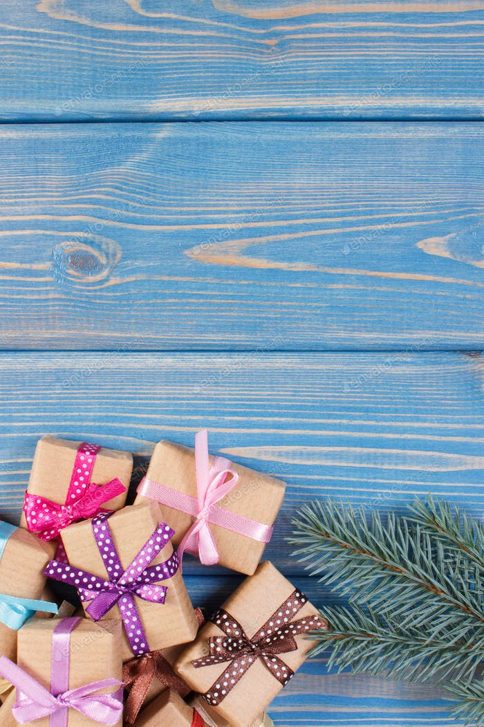 Wrapped gifts with colorful ribbons for Christmas and spruce branches, copy space for text