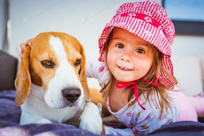 Kind spielt mit Beagle Hund bester Freund im Garten am sonnigen Frühlingstag