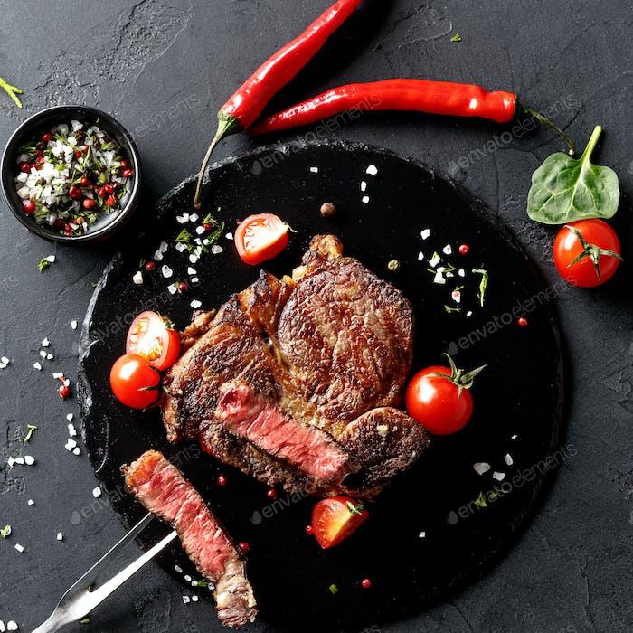 Rare rib eye steak on dark plate, top view