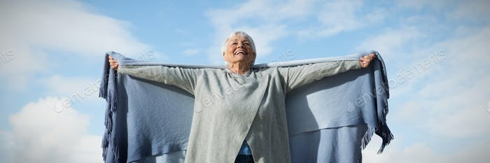 Composite image of happy elder woman raising her arms up