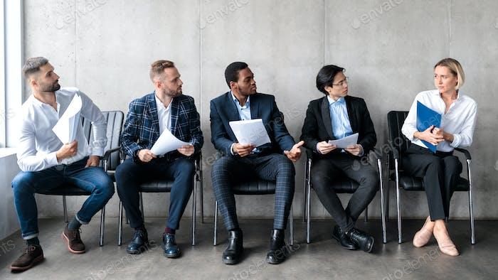 Hombres Mirando a la Mujer Solicitante Esperando Entrevista de Trabajo en el interior