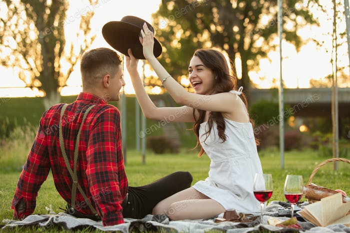 Caucasian young and happy couple enjoying a picnic in the park on summer day