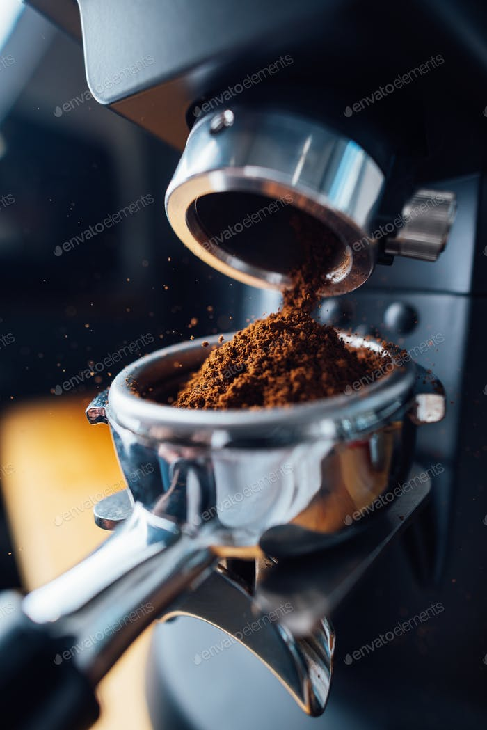 ground coffee pouring into a portafilter with a grinder