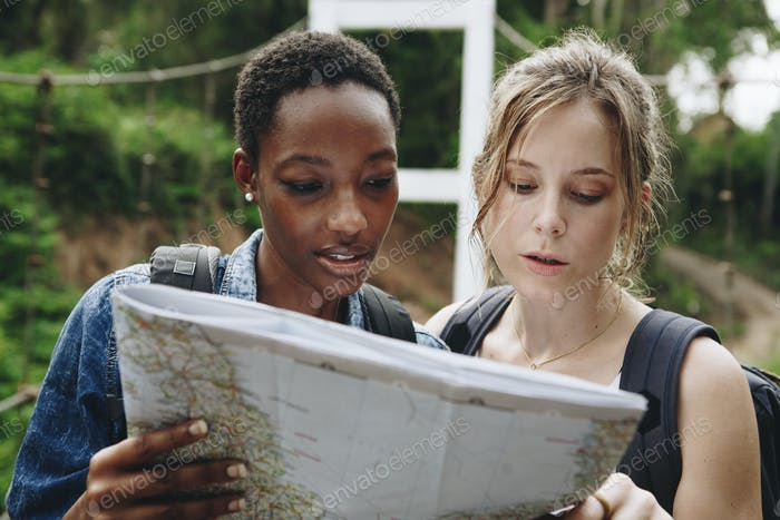 Two women friends looking at a map together travel and teamwork concept
