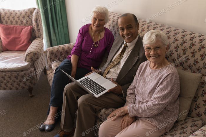 Senior friends with laptop sitting on sofa and looking at camera in home