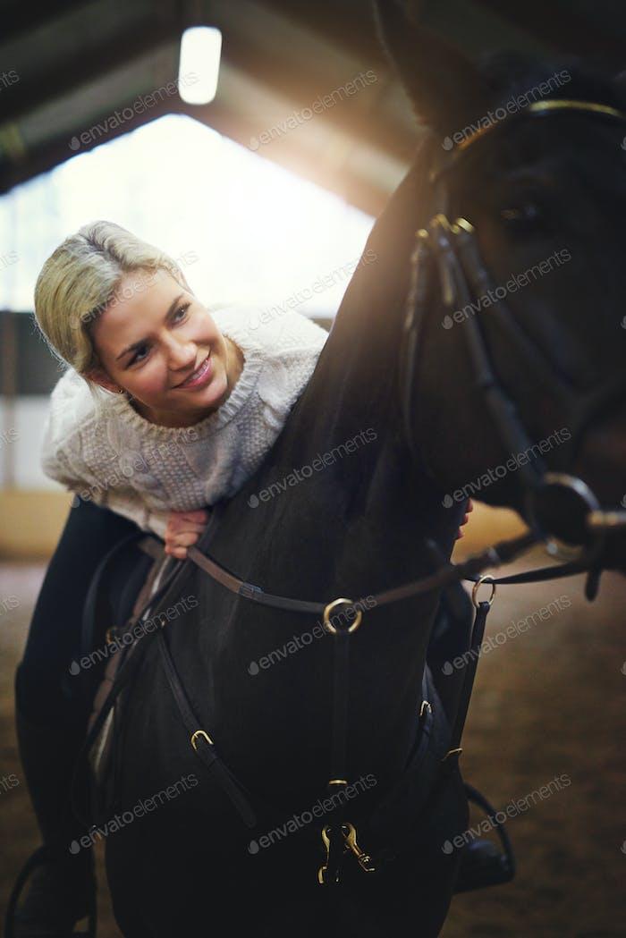 Smiling blonde female sitting astride black horse
