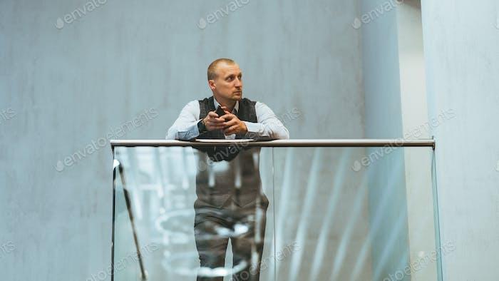 Hombre de negocios en balcón de cristal