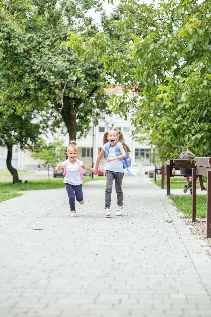 Funny children run to school. The concept of school, study, education, friendship, childhood.