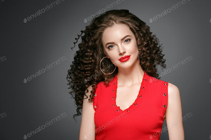 Beautiful curle hair female in red with red lips and dress manicure, beauty red afro hairstyle