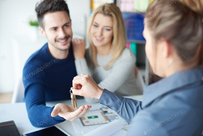 Female realtor handing keyring to man