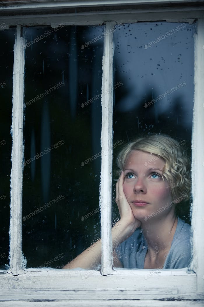 Bored Woman Looking at the Rainy Weather By the Window
