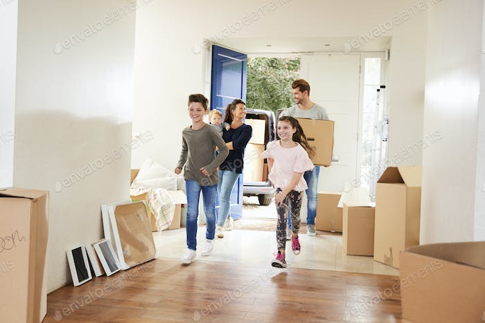 Family Carrying Boxes Into New Home On Moving Day