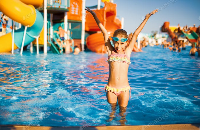 Adorable girl in goggles for swimming standing in the pool and sprinkles raising her hands up