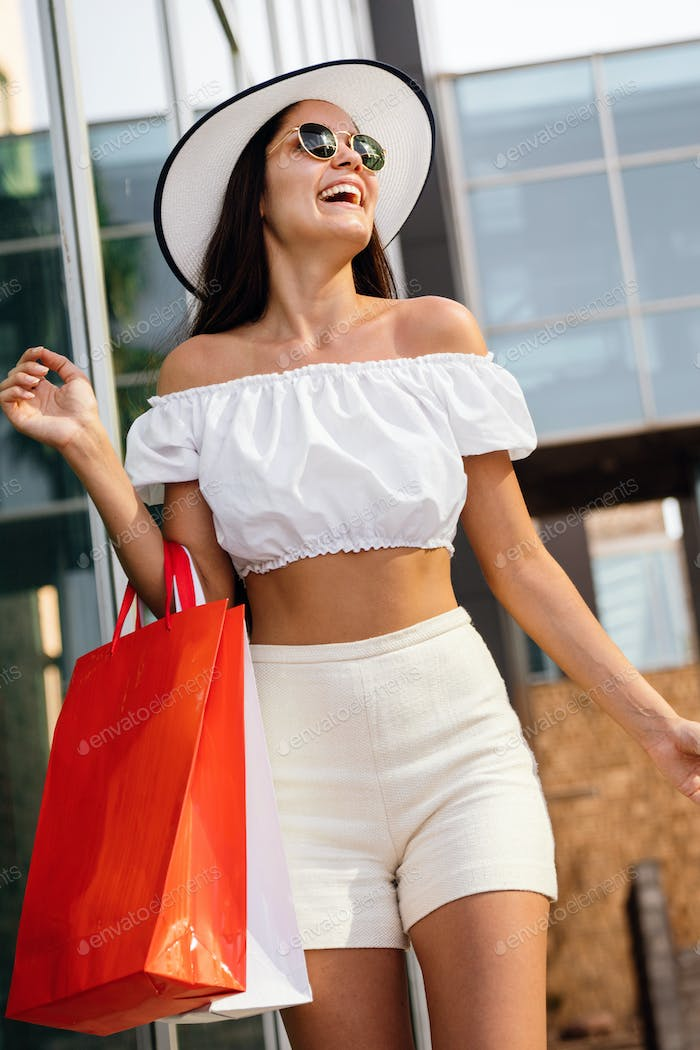 Sale, shopping, tourism and happy people concept. Beautiful woman with shopping bag