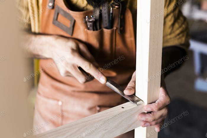 Midsection of carpenter's hands using chisel in workshop