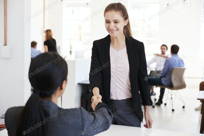 Two women shaking hands at a meeting in an open plan office