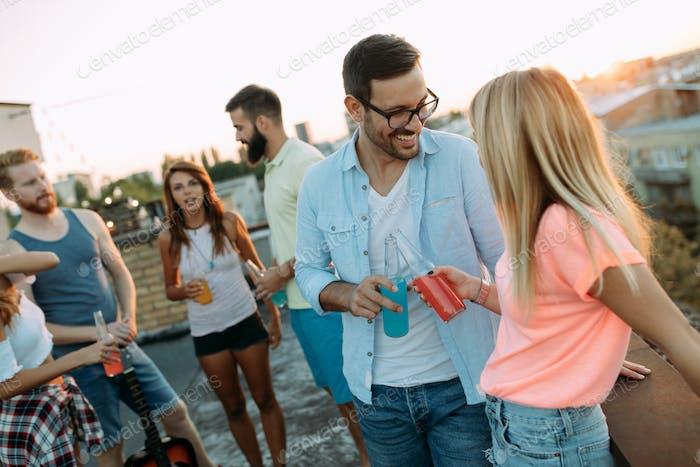 Gruppe von glücklichen Freunden mit Party auf dem Dach