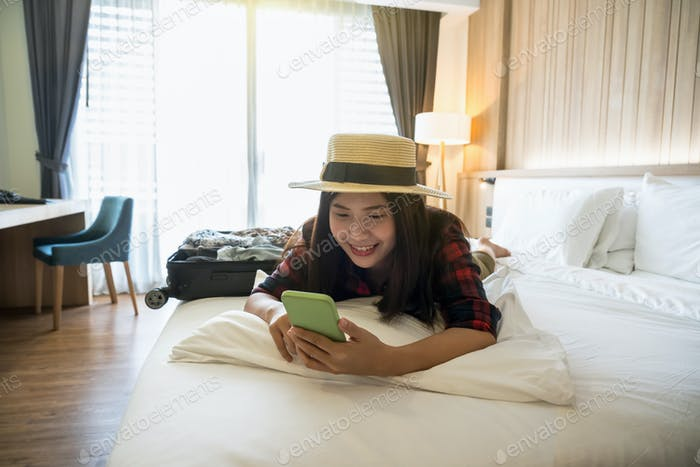 Happiness Asian traveler woman sleeping and using the smart mobile phoneon the bed in bedroom