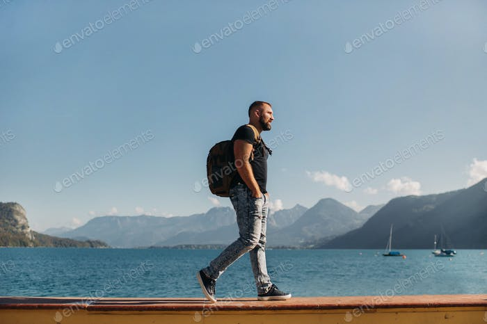 Male traveler with a backpack on the background of Alpine mountains and lakes. Vacation in the Alps