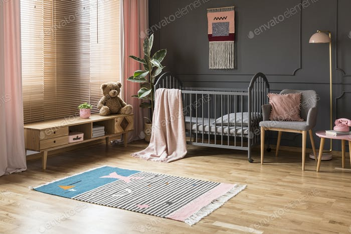 Real photo of a baby crib standing between a low cupboard and an