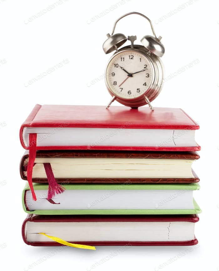 Stack of notebooks with bookmarks and alarm clock