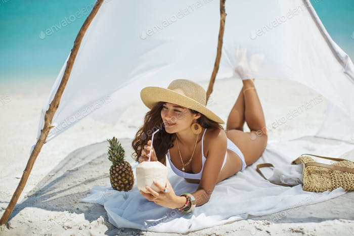 Woman Drinking Coconut Juice while Relaxing on the Beach