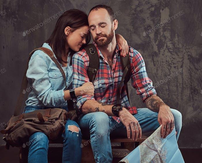 Feliz pareja de turistas con mochila y mapa, abrazándose mientras se sienta en un banco en un estudio.