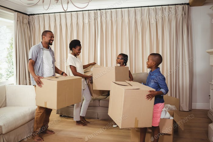 Parents and kids holding cardboard boxes in living room