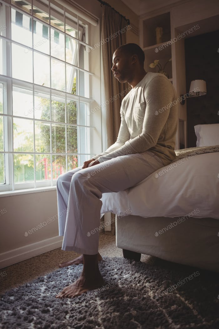 Full length of thoughtful man sitting on bed by window