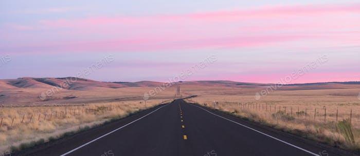 Dawn Breaks over Long Two Lane Road Blacktop Highway