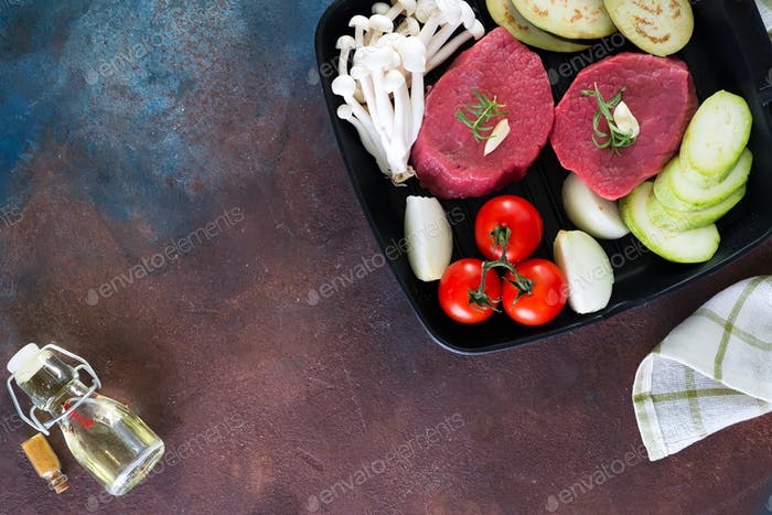 Raw beef steak on the bone with fresh vegetables in a pan on a dark stone background, top view copy