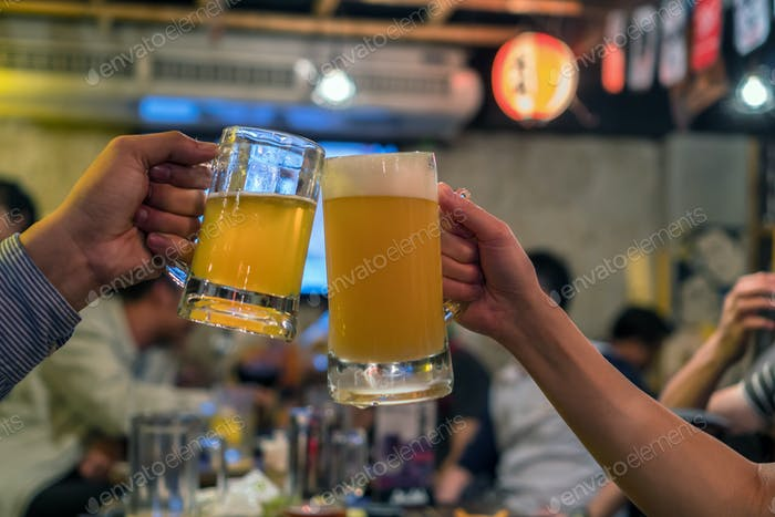 Two Glasses of Beer cheers together between friend in the bar and restaurant