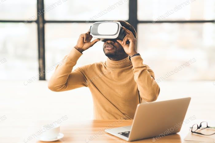 Afro businessman wearing augmented reality goggles at home