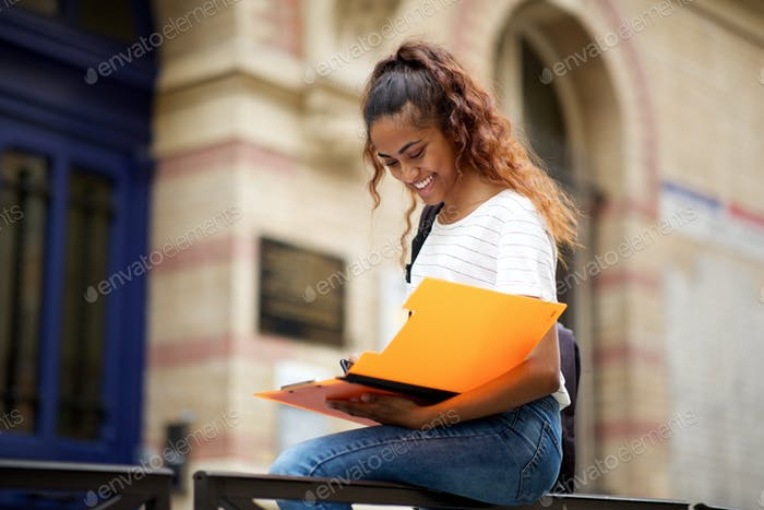 female college student reading notes outside on campus