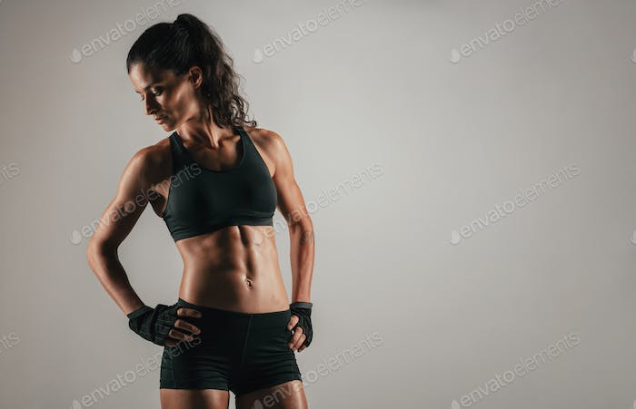 Woman looking back while flexing abdominal muscles