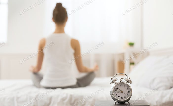 Early awakening. Woman practicing yoga in the morning