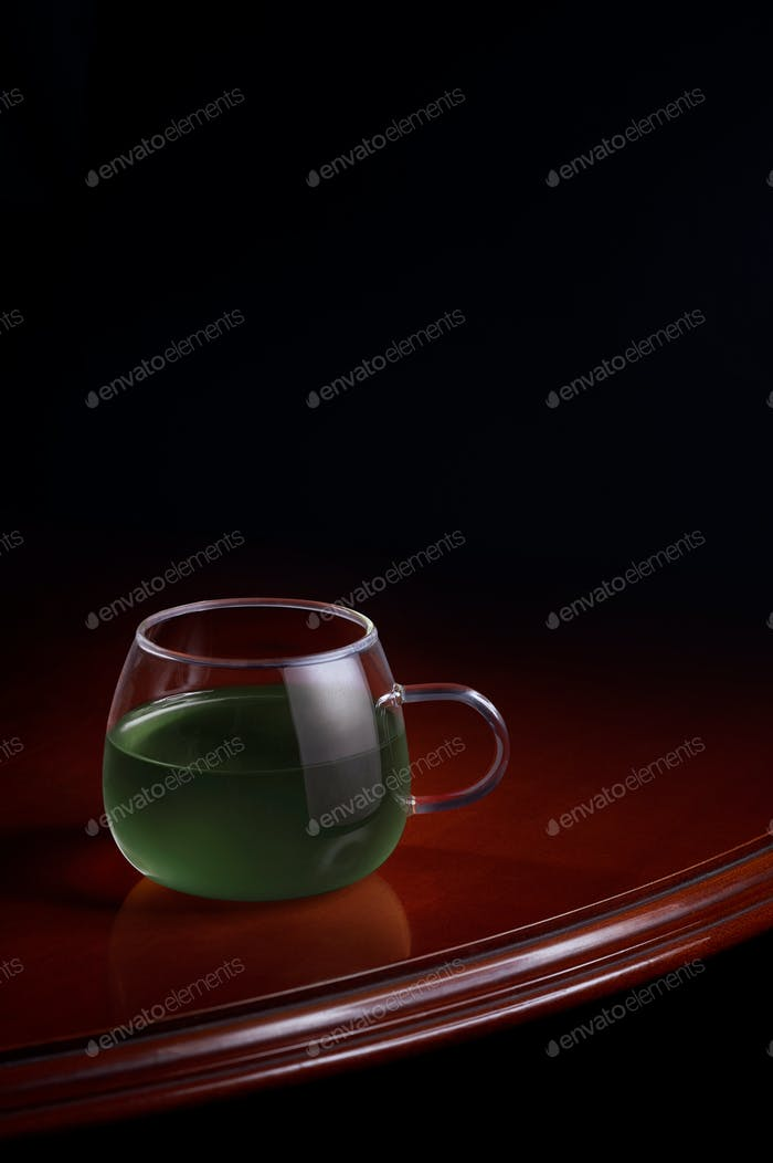 Cup of a green infusion on a luxurious table with a black background