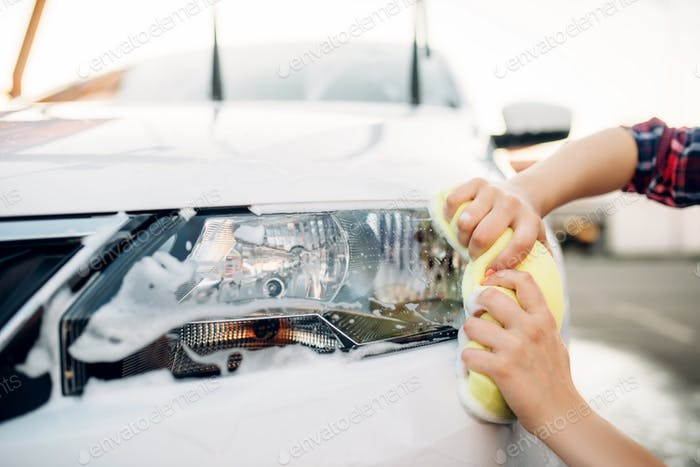 Female person with sponge cleans vehicle headlight