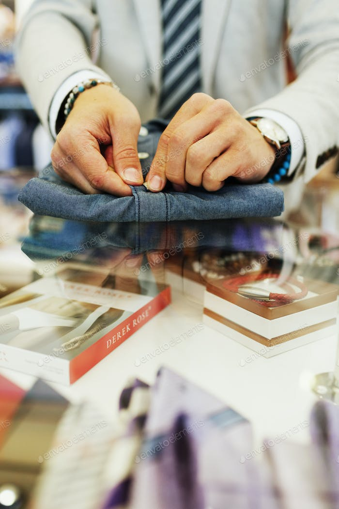 Midsection of salesman buttoning shirt in clothing store