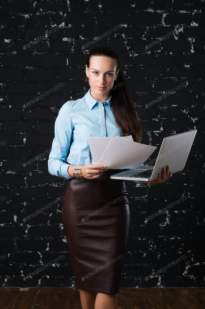 Businesswoman standing and holding laptop, front view.